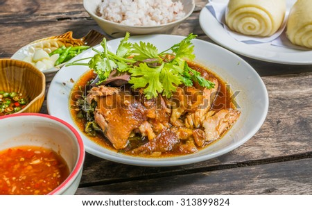 Thai Style pork leg pot stewed(Kao Kha Moo) with rice in white dish on wood table
