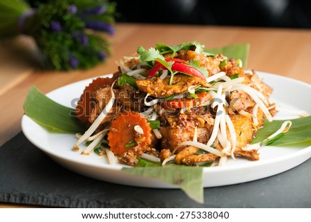 Thai style radish cakes dish with chicken.  Also referred to as turnip cakes. Shallow depth of field. - stock photo