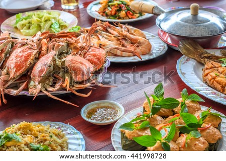 Thai style set of seafood insist of Thai steamed curry fish in banana leaf cups decorated with basil leaf, (Hor Mok Pla) steamed crab/prawn/shrimp with seafood sauce - stock photo