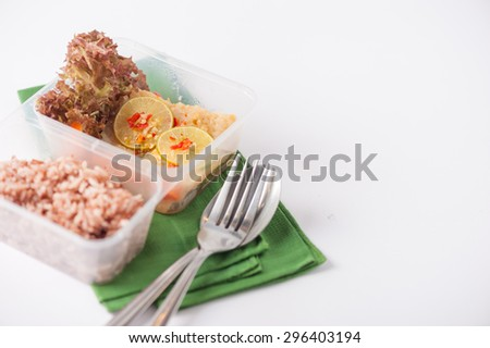 Thai style steamed fish in spicy lemon sauce cooked by clean food concept with vegetables and brown rice in lunch box - stock photo