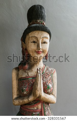 Thai style wooden woman statue doing Sawasdee