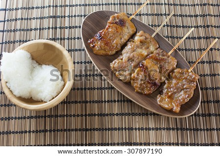 Thai-styled grilled pork and sticky rice. It's among most popular street foods in Thailand. - stock photo