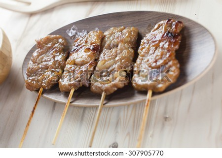 Thai-styled grilled pork. It's among most popular street foods in Thailand. - stock photo