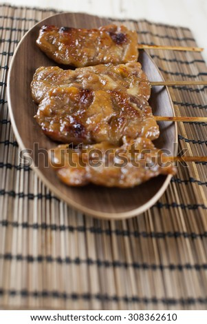 Thai-styled grilled pork on the mat. It's among most popular street foods in Thailand.  - stock photo