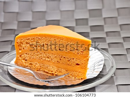 Thai tea layer cake on glass plate with fork