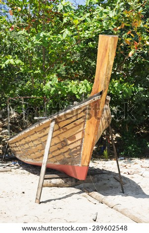 Thai traditional boat is manufacture right on the beach - stock photo
