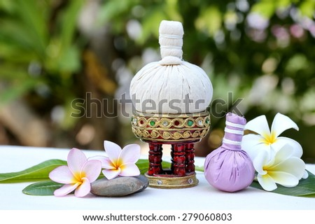 Thai traditional medicine. Body herbal ball. Decorated with white pink frangipani flowers and green leaves. The background is white cotton
