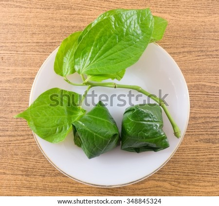 Thai Traditional Snack and Dessert, Top View of Miang Kum or Sweet and Spicy Betel Leaf Wrap Filled with Coconut, Peanuts, Dried Shrimp and Chiles with Lime Sauce.