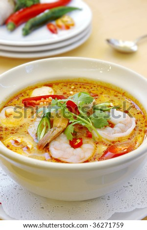 thai traditional tom yam kung soup in a white bowl - stock photo