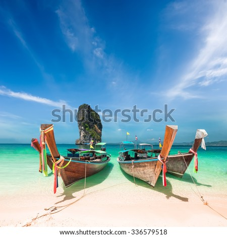 Thai traditional wooden boats with ribbon decoration at ocean shore near Koh Poda island. Thailand, Krabi province, Ao Nang - stock photo