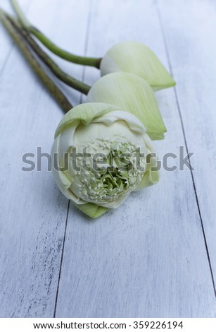 Thai white lotus on wooden table vertical style