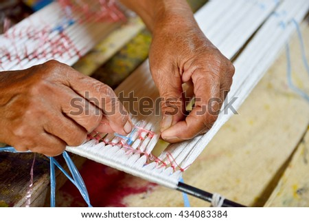 Thai woman hand weaving silk being used to make cloth - stock photo