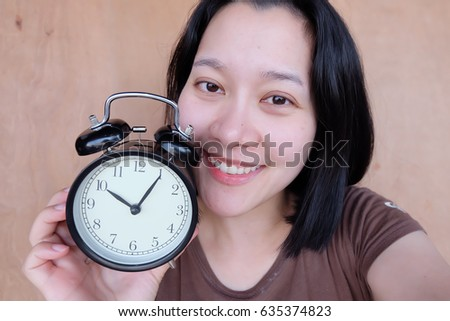 Thai woman holding alarm clock