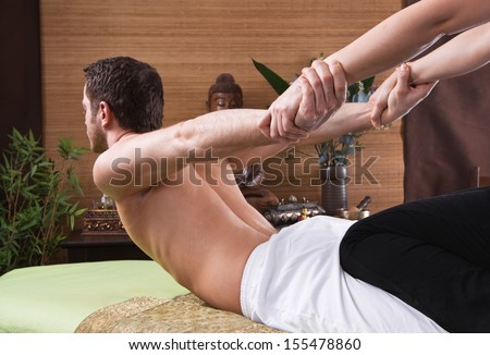 Thai woman making massage to a man - stock photo