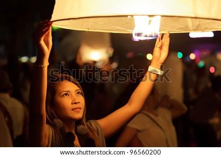 thai woman sending fire lantern during Loi Krathong Buddhist festival in Chiang Mai, thailand - stock photo