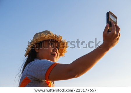 Thai Woman using smartphone at the beach