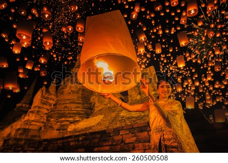 Thai woman with floating lamp in Ayuthaya historical park, with Wat Phra Sri Sanphet temple background, Thailand - stock photo
