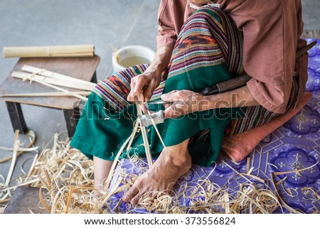 Thai woman working on bamboo using for umbrella in Thailand - stock photo