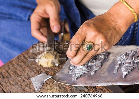 THAILAND - AUGUST 10:A carvers using a tool on a silver plate to carve on August 10, 2013 in Chiangmai,Thailand - stock photo