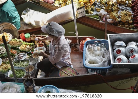 Thailand, Bangkok: 14th march 2007 - Thai woman preparing food on her boat at the Floating Market - EDITORIAL