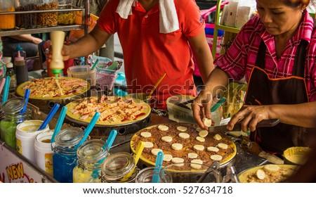 THAILAND BANGKOK 2016 - woman preparing pancakes on a street stall