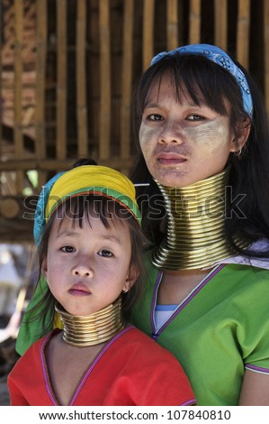 Thailand, Chiang Mai, Karen Long Neck hill tribe village (Baan Tong Lhoung), Long Neck woman with her child in traditional costumes. Women put brass rings on their neck when they are 5 or 6 years old - stock photo