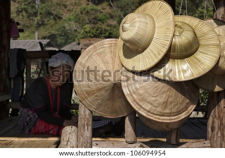 Thailand, Chiang Mai, Karen Long Neck hill tribe village (Kayan Lahwi), a Karen woman in traditional costumes and oriental hats for sale - stock photo