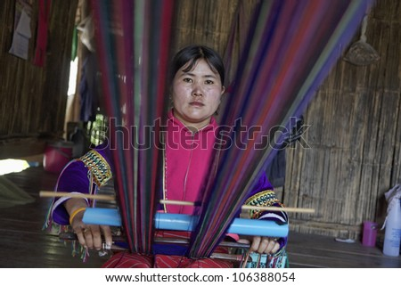 Thailand, Chiang Mai, Karen Long Neck hill tribe village (Kayan Lahwi), Karen woman in traditional costumes is making a carpet - stock photo