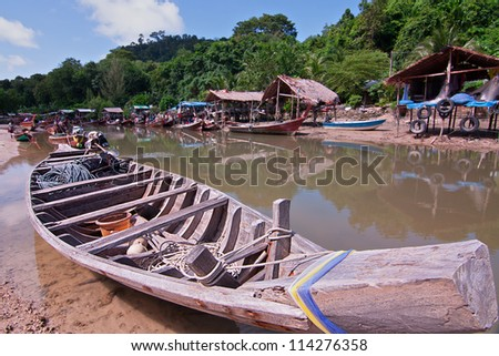 Thailand fishing village along a muddy river showing traditional long tail boats
