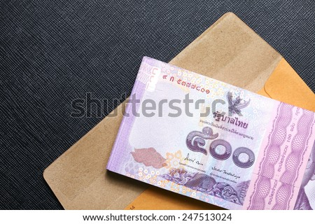 Thailand five hundred baht banknotes put on the brown color paper envelope represent the Thai financial and monetary  related.