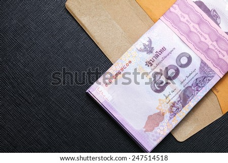Thailand five hundred baht banknotes put on the brown color paper envelope represent the Thai financial and monetary  related. - stock photo