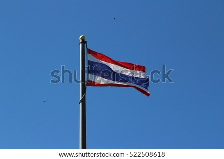 Thailand flag waving in the wind with a blue sky background.
