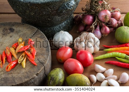 Thailand Food Ingredients: Tomatoes, peppers, garlic, shallots, lemon, olive on a wooden floor.