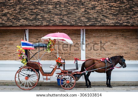 Thailand Horse Carriage Side View with Brick Wall - stock photo