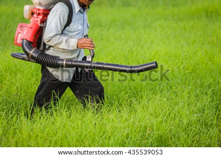 Thailand Man farmer to herbicides or chemical fertilizers on the fields green rice growing.