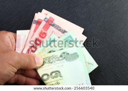 Thailand one hundred baht and twenty baht  banknotes in hand represent the Thai financial and monetary  related. - stock photo