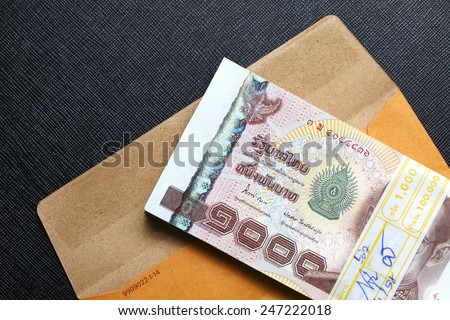 Thailand one thousand baht banknotes put on the brown color paper envelope represent the Thai financial and monetary  related. - stock photo