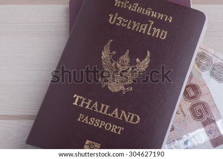 thailand passport and money on wood background
