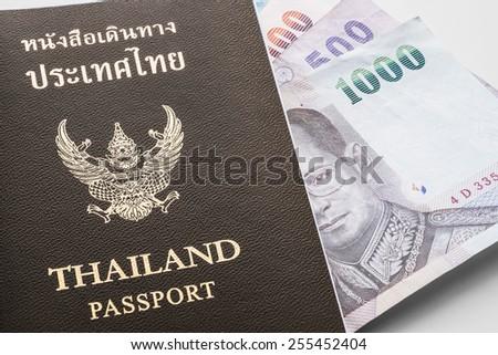 Thailand passport and Thai cash on white background (soft focus) - stock photo