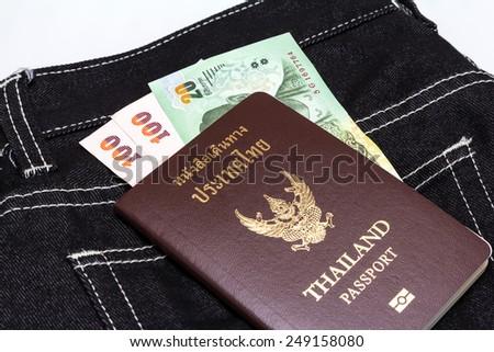 Thailand passport with Thai money  on Jeans pocket - stock photo