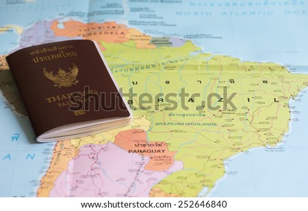 Thailand Passports on a map of the Brazil. - stock photo