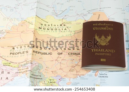 Thailand Passports on a map of the China and Mongolia. - stock photo