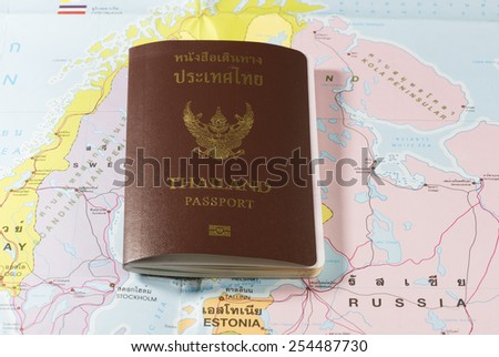 Thailand Passports on a map of the  Estonia and Russia. - stock photo