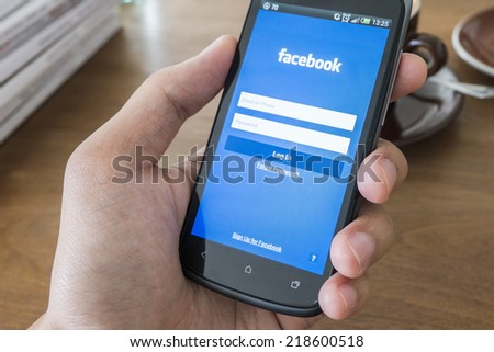 THAILAND - SEPTEMBER 05, 2014: Facebook application login screen on htc mobile with hand holding.