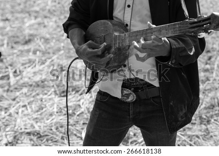 Thailand traditional musician hillbilly playing country folk music in rice paddy field, black and white