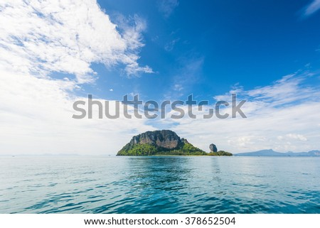Thailand tropical island cliffs over ocean water during tourist boat trip in Railay Beach resort - stock photo