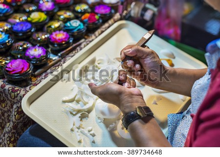 Thailander carving soap flower in a night market. - stock photo