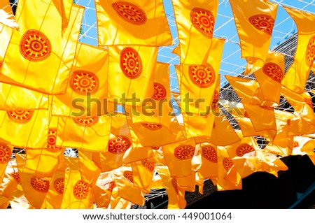 Thammachak flag yellow in temple (Wat Phan tao) on blue sky temple Northern Thailand - stock photo