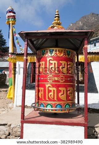 Thamo gompa with prayer flags and buddhist symbols - monastery in Khumbu valley on three passes trek, Mount Everest area, Sagarmatha national park, Nepal - stock photo