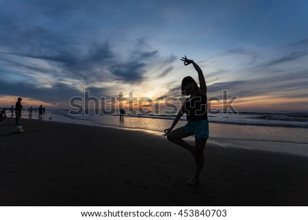 Thanh Hoa, Vietnam , Aug 13 2015 , Young healthy woman practicing yoga on the beach at sunset